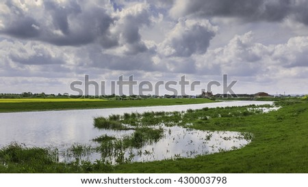 Wilfholme, Yorkshire, UK. The River Hull at high tide showing the river bank and surrounding fields and farmhouse with cloudy sky near Wilfholme, Yorkshire, UK. - stock photo