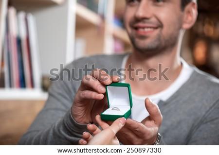 Will you marry me. Low angle portrait with selective focus of handsome young man making a proposal while giving an engagement ring to his girlfriend  - stock photo