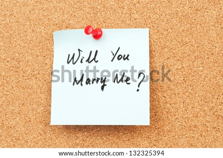 Will you marry me words written on paper and pinned on cork board - stock photo