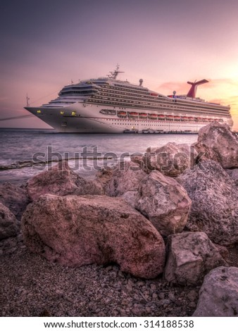 Willemstad, Curacao  - May 27, 2015: The Carnival Conquest is docked in the port of Curacao at sunset - stock photo