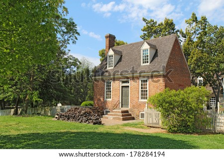 WILLIAMSBURG, VIRGINIA - APRIL 21 2012: A small brick building in the center of Colonial Williamsburg in Virginia. The restored town is a major attraction for tourists and meetings of world leaders. - stock photo
