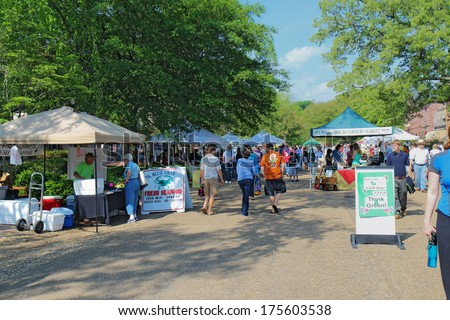 WILLIAMSBURG, VIRGINIA - APRIL 21 2012: Vendors and shoppers at the Williamsburg Farmers Market in spring. The restored town is a major attraction for tourists and meetings of world leaders.
