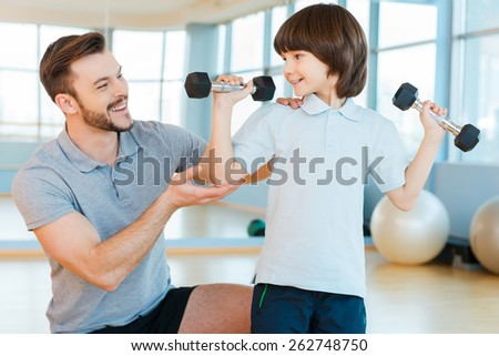 Willing to be strong and healthy. Happy father helping his sun with weight exercises while both standing in health club  - stock photo