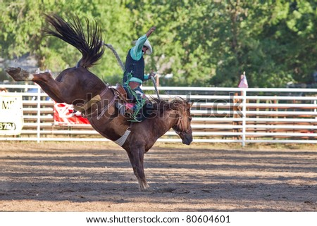 WILLITS, CA - JULY 4: Another rodeo rider trying to stay on a twisting horse at the Willits Frontier Days, California's oldest continuous rodeo, held July 4, 2011 in Willits, CA. - stock photo