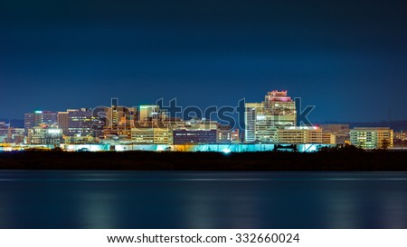 Wilmington skyline by night, viewed from New Jersey, across the Delaware River. Wilmington is the largest city in the state of Delaware. - stock photo