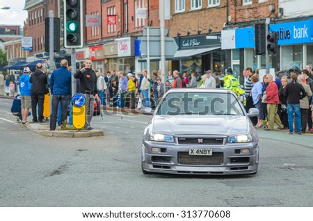 Wilmslow UK - July 9, 2013 : A Nissan Skyline GTR drives sideways during the annual public gathering of local sports and super cars in affluent Wilmslow, Cheshire - stock photo