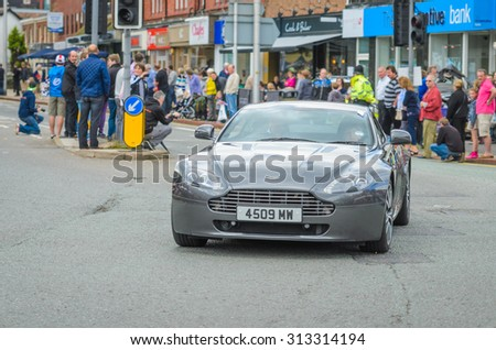 Wilmslow UK - July 9, 2013 : An Aston Martin drives sideways during the annual public gathering of local sports and super cars in affluent Wilmslow, Cheshire - stock photo