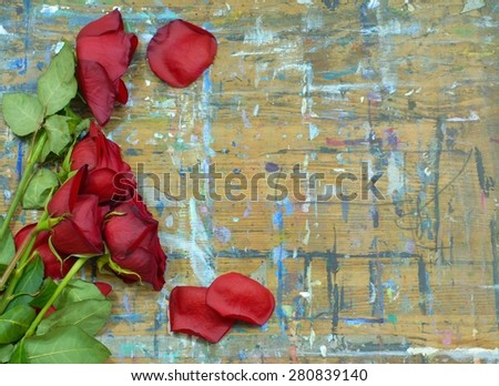 Wilted and faded red roses and green stems on a wood surface with multiple paint stains. Some fallen rose petals are scattered around. Concept of age or old love. Copy space on right.  - stock photo