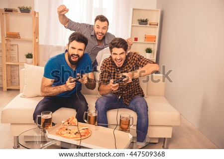 win! excited happy cheerful men play video game with beer and pizza at home - stock photo