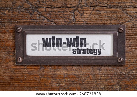 win-win strategy  - file cabinet label, bronze holder against grunge and scratched wood - stock photo