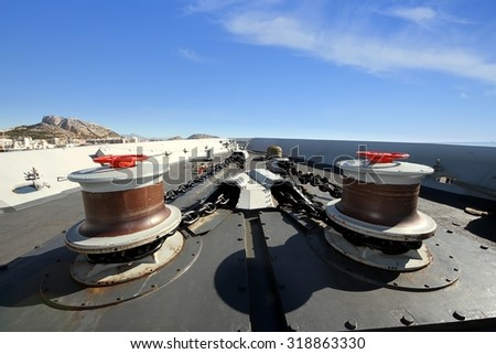 Winches and big chain for the anchor of a warship - stock photo