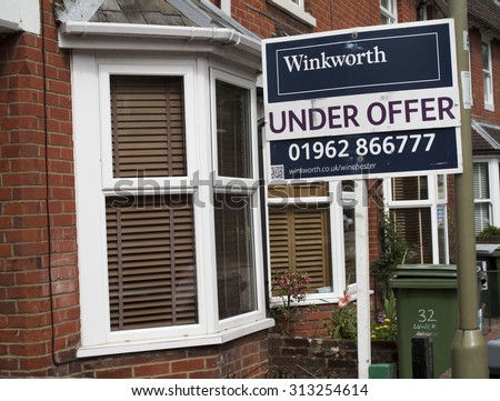 Winchester, Hampshire, England - September 4, 2015: Estate agent residential under offer house for sale sign - stock photo