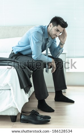 Wincing businessman sitting at edge of bed at home in bedroom