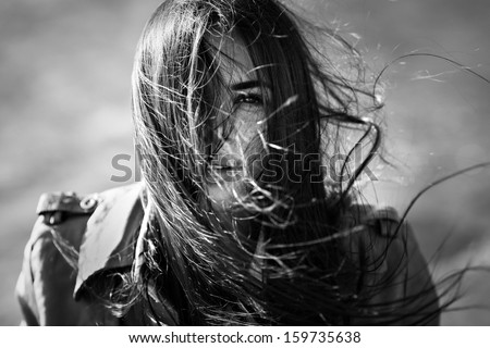 wind blowing hair of beautiful woman, outdoors, black and white - stock photo