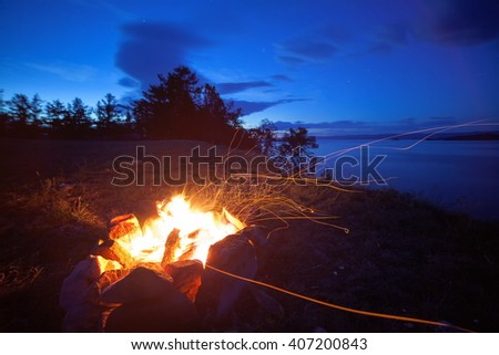 Wind blowing sparks Bonfire night on the shores of Lake Baikal.