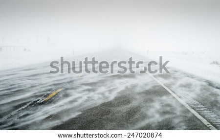 Wind blown snow covered winter roads Colorado - stock photo