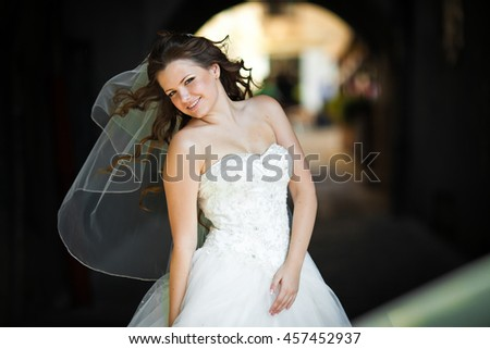 Wind blows bride's long hair away while she stands on the street