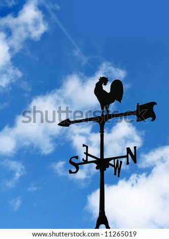 Wind cock direction on blue cloudy sky - stock photo