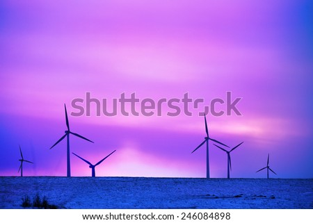 wind driven electric plant in firstlight on snow - stock photo