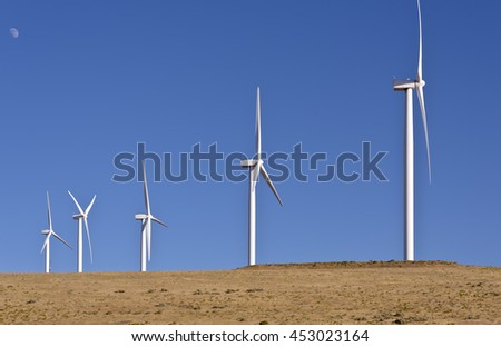 Wind eneregy generated by large blades spinning on a hill in Oregon.