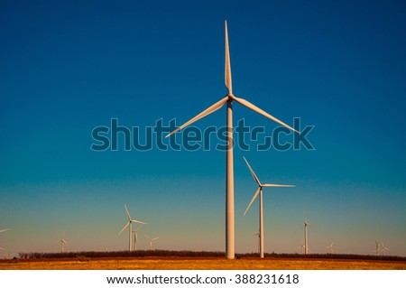Wind Energy Blows into Future Amarillo and West Texas Wind Turbine Farms in the lone star state at colorful sunset with all colors of the rainbow showing renewable energy works