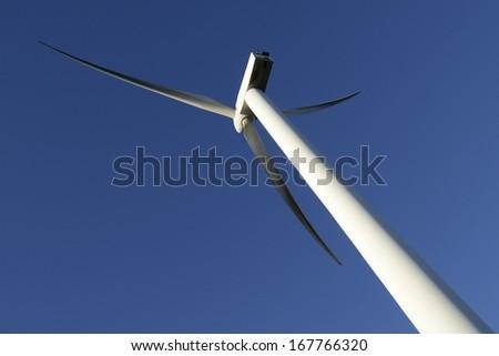 Wind energy business. Wind turbine closeup with blue sky background - stock photo