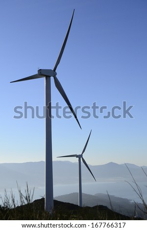 Wind energy business. Wind turbines silhouette and closeup with blue sky