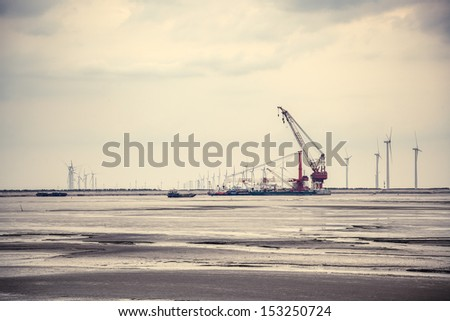 wind energy constructed at the mud flat near sea shore - stock photo