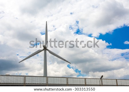 Wind energy. Image of single white wind turbine located inside power plant massive clouds and dramatic blue sky background.  - stock photo
