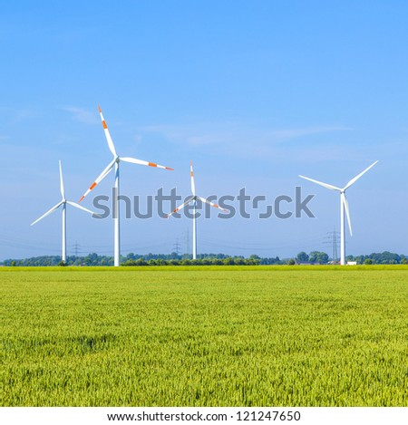 Wind energy wovers standing in the field in spring - stock photo