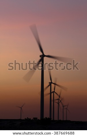 wind/eolian power turbine in motion, with sunset background
