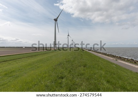 Wind farm along the dike of the noordoostpolder in the Netherlands - stock photo