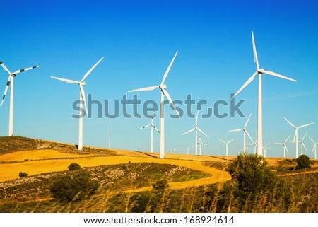 Wind farm at farmland in summer. Aragon - stock photo