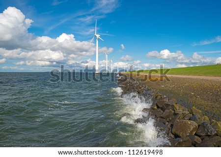 Wind farm in a stormy lake - stock photo