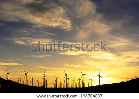 wind farm in silhouette at sunset