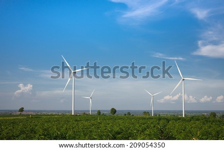wind farm on rural terrain with cloudy blue sky