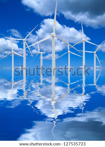 Wind farm reflecting in water with blue sky and clouds.