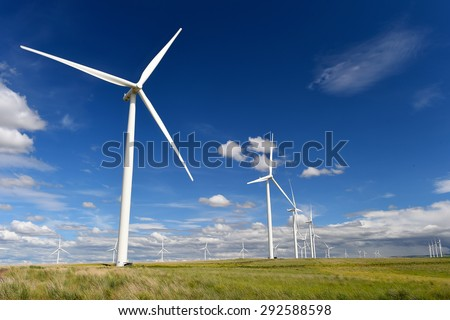 wind farm turbines white contrast green grass and blue sky, washington state, united states - stock photo