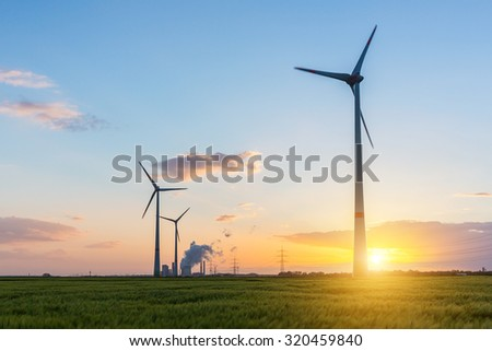 wind farm with coal power plant at sunset - stock photo