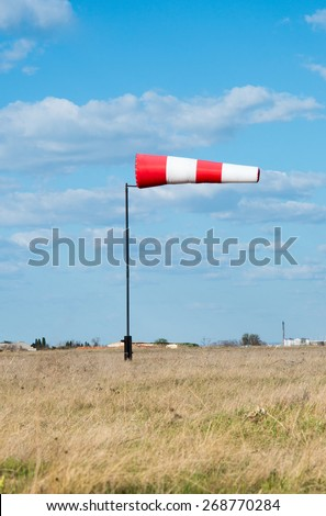 Wind flag windsock on the background of blue sky airport - stock photo