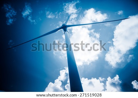 wind generators aganist the blue sky, blue toned. - stock photo