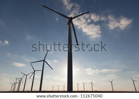 Wind generators field on blue sky.