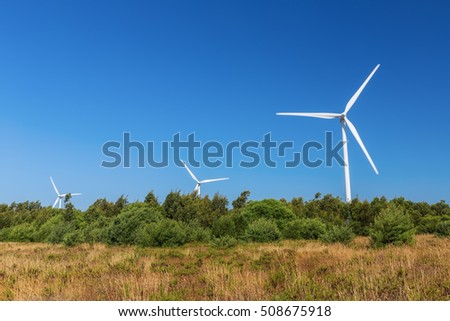 Wind generators line the forest.