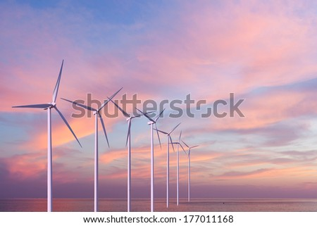 Wind generators turbines in the sea on sunset - stock photo