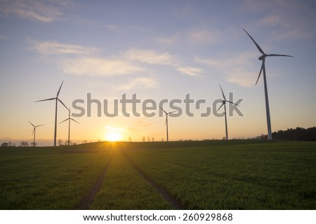 Wind generators turbines on sunset spring landscape