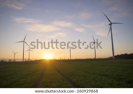 Wind generators turbines on sunset spring landscape  - stock photo