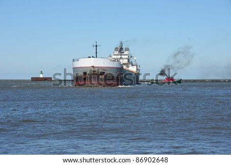 Wind gusts of 25 mph cause a single tug boat to struggle to control the stern of a Great Lakes bulk carrier ship inside the Lake Erie break wall at Cleveland, Ohio - stock photo