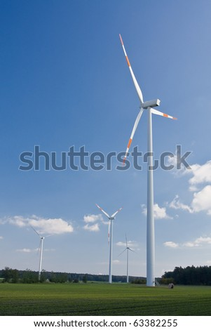Wind mill in green field with clouds - renewable energy source concept