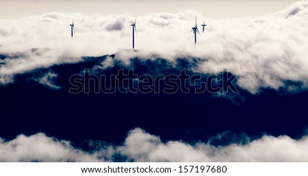 Wind mills generating electricity in the clouds / alternative energy / beautiful view - stock photo