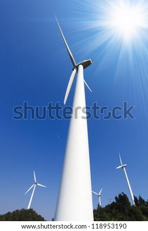 wind power against a blue sky with sun rays - stock photo